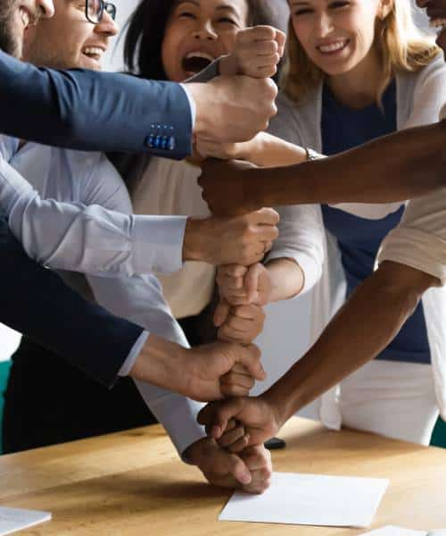 Group of Business professionals placing hand one above another which indicated teamwork