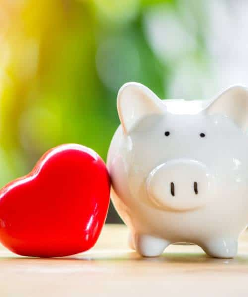Heart and piggybank placed together on a table