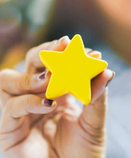 Hand holding yellow star with background blur
