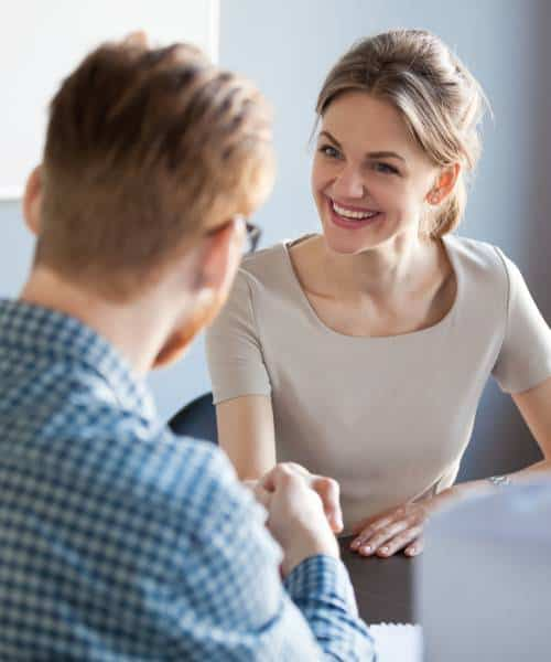 Smiling woman having a handshake with his portfolio manager