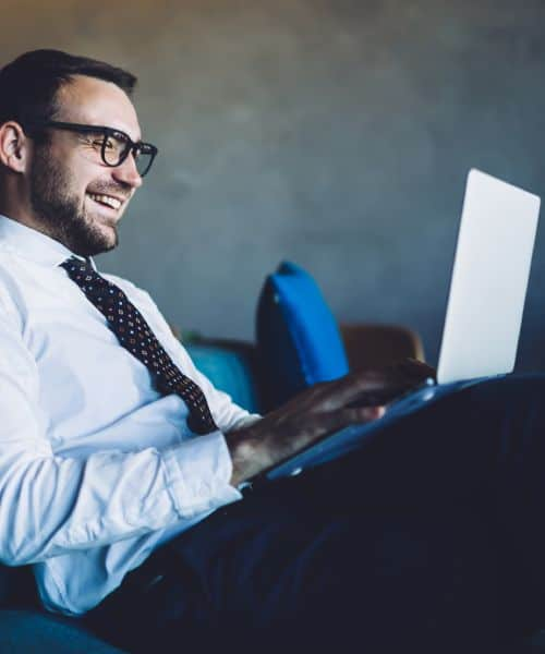 A happy businessman sitting on a blue sofa and working on his laptop