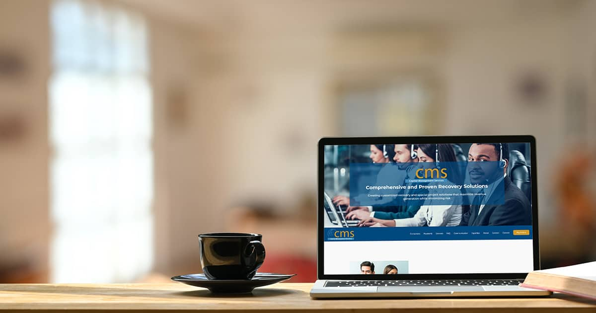 Photo of white blank screen laptop, black coffee cup and coasters on the wooden working desk over blurred modern cafe background.