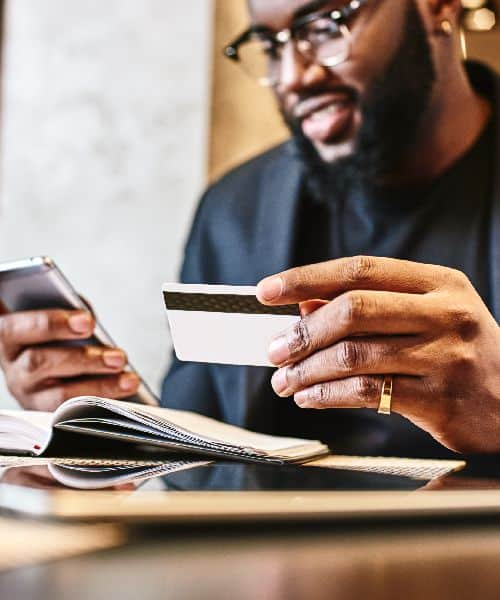Man making an online payment from the phone through his credit card